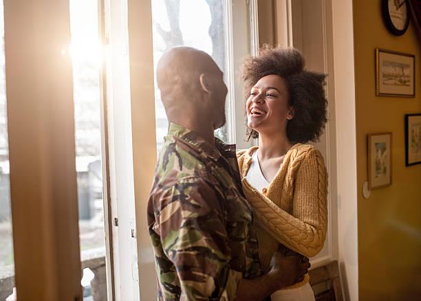 Gaie femme afro-américaine parler à son mari militaire. - Photo