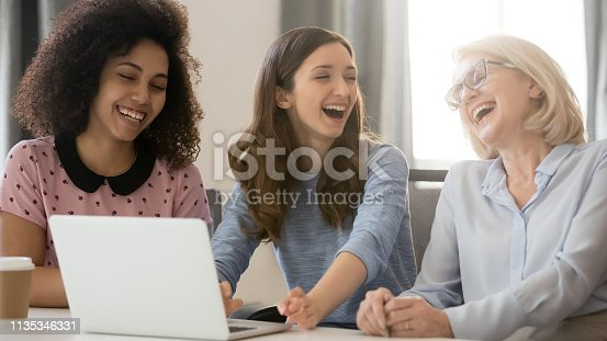 1166905017 istock photo Cheerful african and caucasian businesswomen laughing having fun at workplace 1135346331