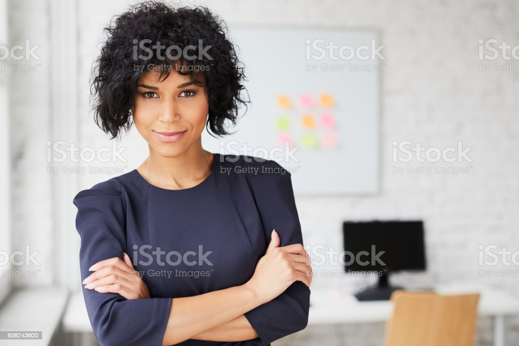 Cheerful african business woman smiling at creative office stock photo