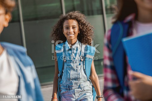 istock Cheerful african child girl with backpack going to school with fun and looking in camera 1175711436