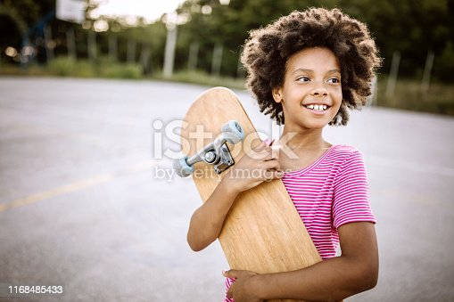 Cheerful African girl with curly hair holding skateboard and smiling happily