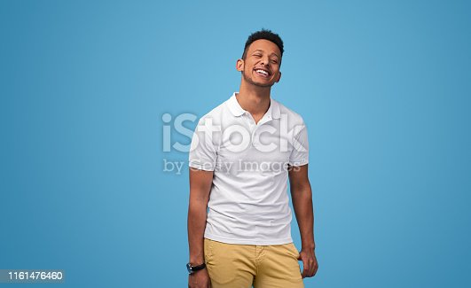 Stylish black man in white polo shirt smiling and keeping eyes closed while standing against blue background