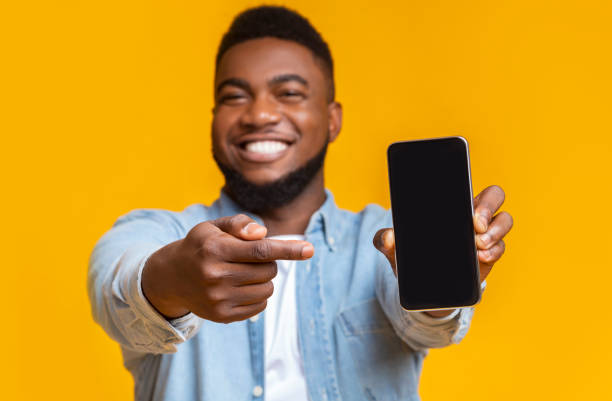Cheerful african guy pointing at smartphone with black screen stock photo