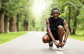 Cheerful african guy tying laces on his sneakers before training, jogging by park, empty space