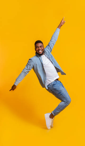 Cheerful African Man Standing On Tiptoes, Fooling Over Yellow Background stock photo