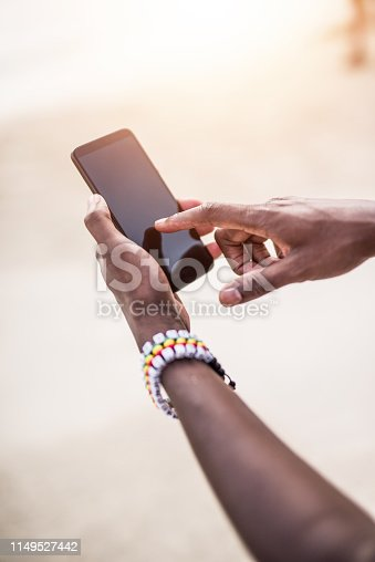 Cheerful African man using a phone while on a beach.