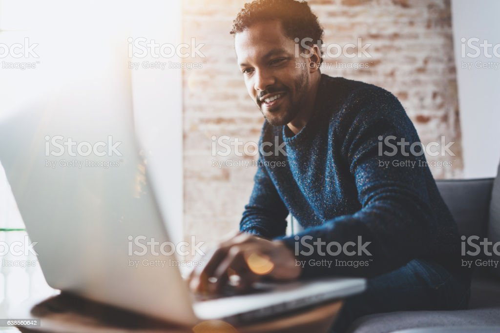 Cheerful African man using computer and smiling while sitting on stock photo
