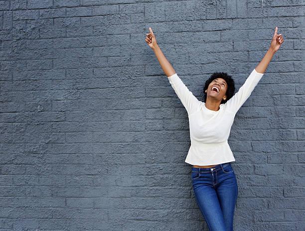 fröhlich afrikanische frau mit händen hoch zeigen sie - dynamische posen stock-fotos und bilder