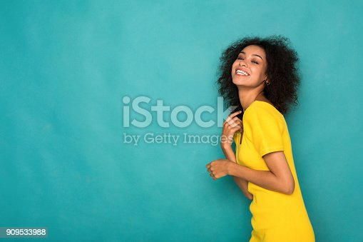 istock Cheerful african-american girl posing at studio 909533988