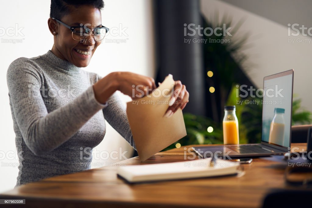 Cheerful afro american businesswoman in trendy eyewear feeling happy getting letter with documents for successful project,happy female freelancer satisfied with occupation receiving job offer paper stock photo