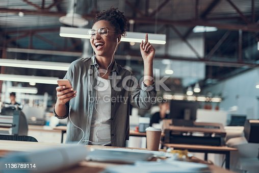 Waist up portrait of charming young lady in earphones holding cellphone and enjoying favorite songs. She is raising finger up, moving to the rhythm of music and laughing