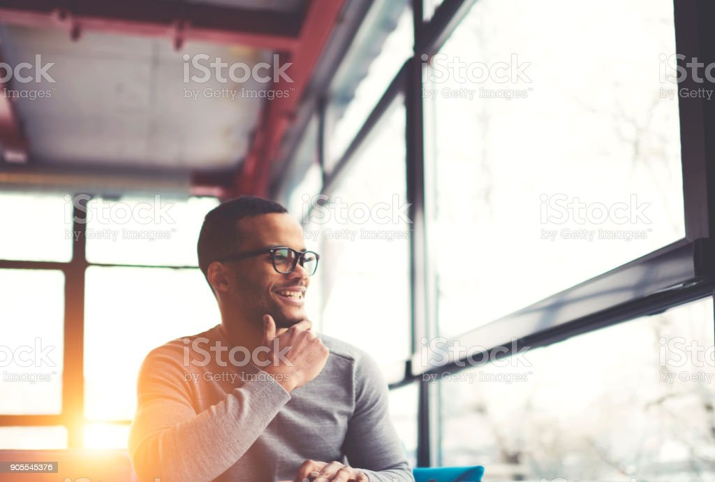 Cheerful afro american hipster guy in trendy spectacles sitting in loft interior cafe resting in good mood, smiling young dark skinned businessman satisfied with successfully completed project stock photo