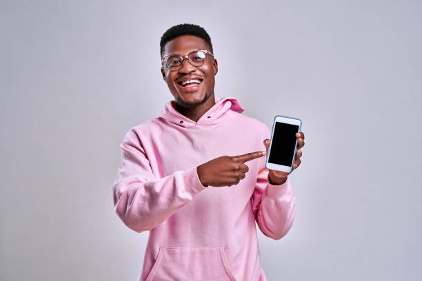Cheerful afro american man dressed in a pink hoodie and glasses holds a phone and shows on his screen. The concept of gadgets and advertisements. stock photo