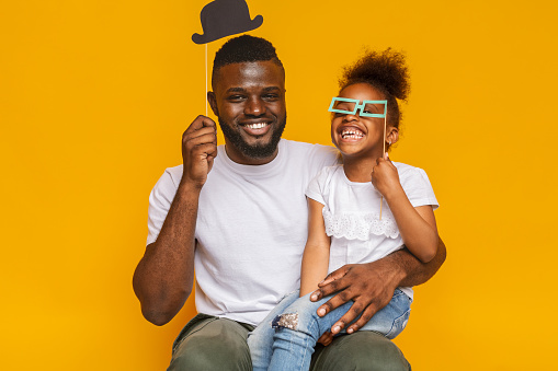 istock Cheerful afro father and daughter posing with photo props 1174500891