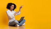Online Offer. Cheerful Afro Girl Sitting On Floor With Laptop And Pointing Away With Fingers, Indicating Copy Space On Yellow Background, Panorama