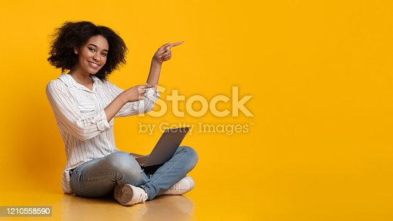 istock Cheerful Afro Girl Sitting On Floor With Laptop And Pointing Aside 1210558590