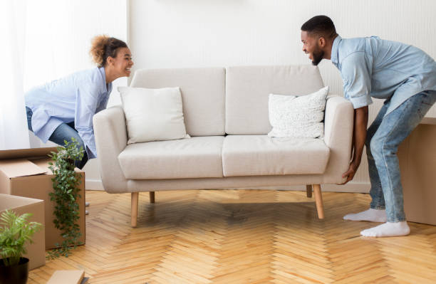 Cheerful Afro Spouses Placing Couch Furnishing Empty Room In New House Moving Concept. Cheerful Afro Spouses Placing Couch Furnishing Empty Room In New House After Relocation physical activity stock pictures, royalty-free photos & images