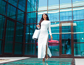 istock Cheerful Afro woman in white beautiful dress holding many paper shopping bags while walking  at front of business building with blue windows. Shopaholic concept. 1170150517