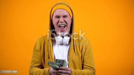 Cheerful aged dj in stylish clothes holding dollar notes and listening to music