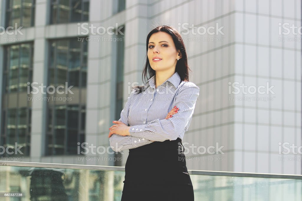 Cheerful and confident. Portrait of beautiful young business woman in smart casual wear keeping arms crossed while standing against office building. foto stock royalty-free
