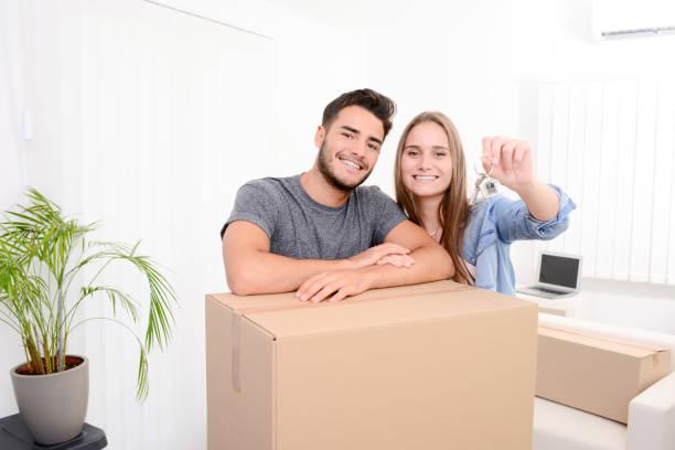 casal jovem alegre e feliz, segurando as chaves da sua nova casa com o movimento cardbox durante mudança para o novo apartamento - vida de estudante - fotografias e filmes do acervo