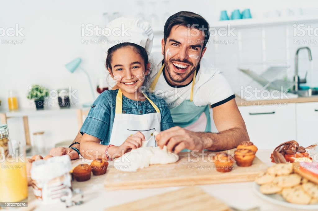 Father and daughter preparing cupcakes together