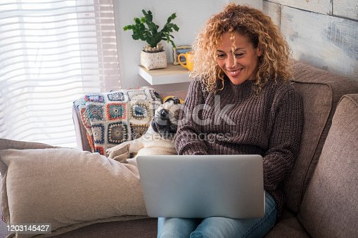 Cheerful and nice couple with people and animal - beautiful culry adult woman with funny dog pug at home using personal computer laptop sitting on the sofa together looking the screen