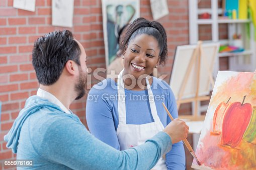 658645980 istock photo Cheerful art instructor works with student 655976160