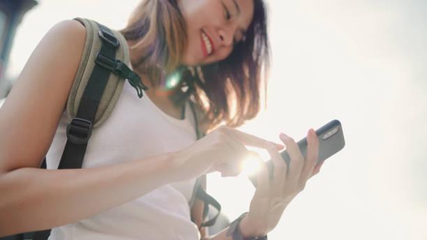 Fröhliche asiatische Backpacker-Blogger-Frau mit Smartphone für die Richtung und auf der Lagekarte, während die Reise in Chinatown in Peking, China. Lifestyle Rucksack Touristie-Reise Urlaubskonzept. – Foto