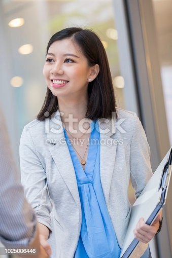 Confident young businesswoman shakes hands with an unrecognizable male client.