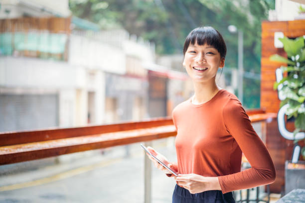 Cheerful Asian businesswoman holding a digital tablet stock photo