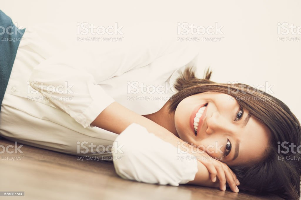 Cheerful Asian businesswoman resting on floor_tone royalty-free stock photo
