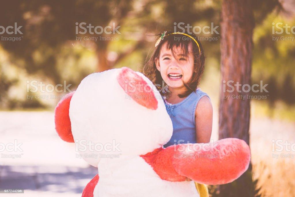 Cheerful Asian girl playing with huge teddy bear in park - Stock image .