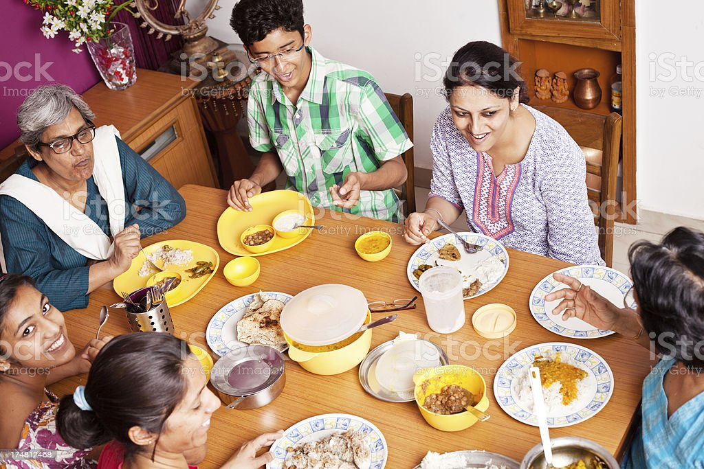 Cheerful Asian Indian Family Enjoying Meal Together royalty-free stock photo
