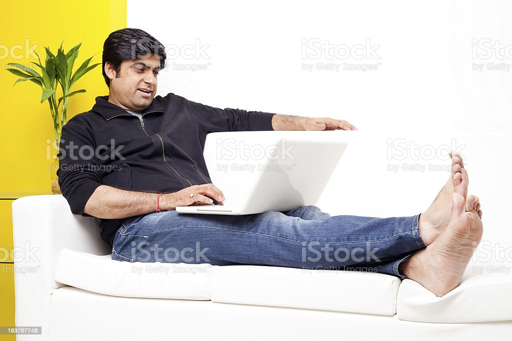 Cheerful Asian Indian Man sitting on Couch Sofa Using Laptop royalty-free stock photo