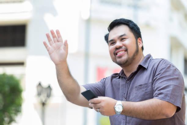 gai homme asiatique est originaire d'un taxi dans une rue - homme faire coucou voiture photos et images de collection