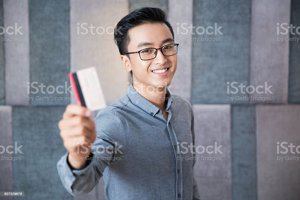 Cheerful Asian man showing credit card to camera stock photo