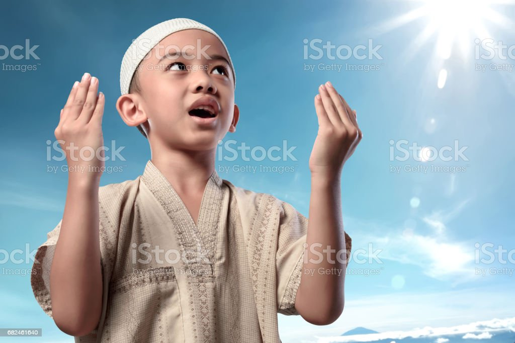 Cheerful asian muslim child in traditional dress praying royalty-free stock photo