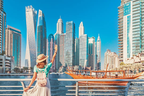 Cheerful asian traveler girl walking on a promenade in Dubai Marina district. Travel destinations and tourist lifestyle in UAE stock photo