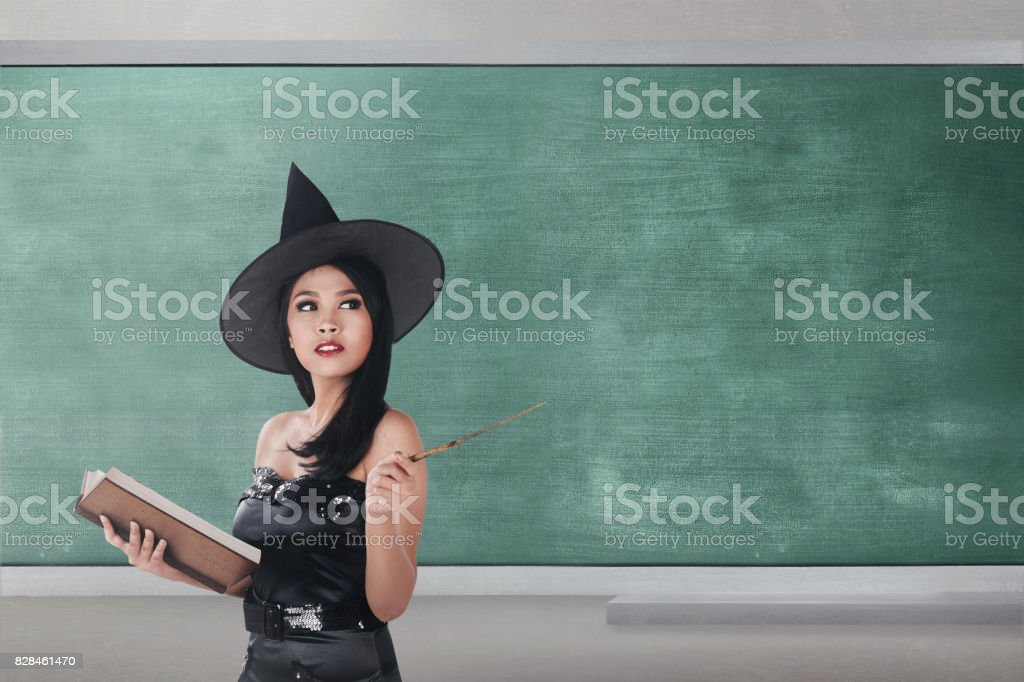 Cheerful asian wizard woman holding book and wand stock photo