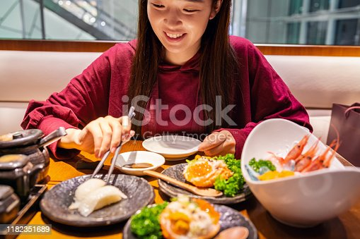 Cheerful Asian woman dining in a Japanese restaurant.