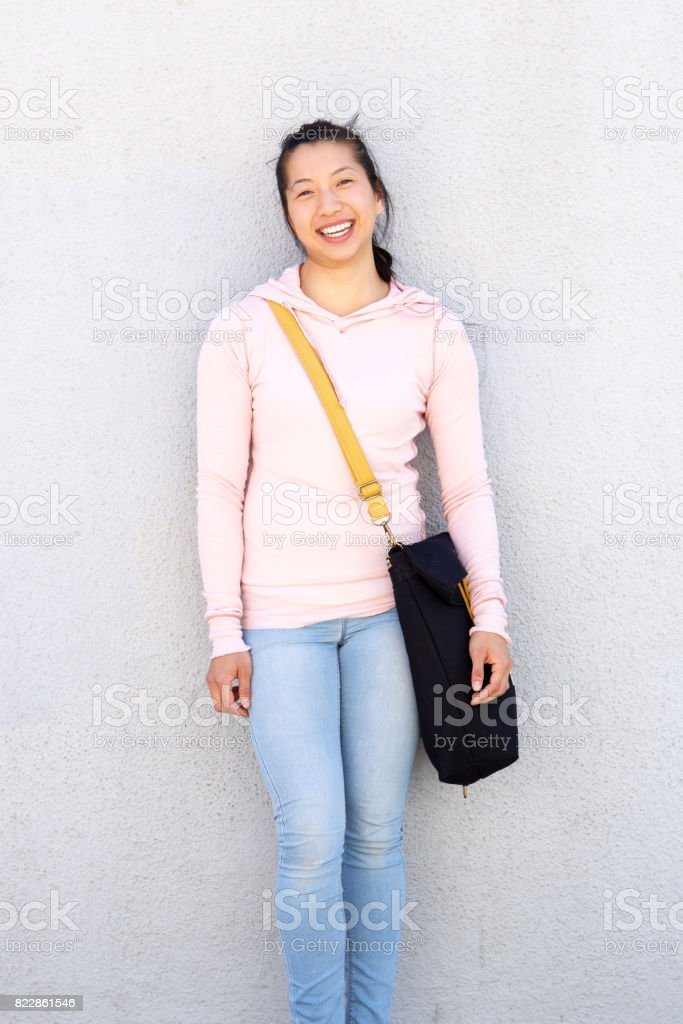 cheerful asian woman standing outside against wall with bag stock photo