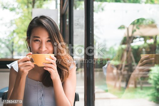Cheerful asian young woman drinking warm coffee or tea enjoying it while sitting in cafe. Attractive happy asian woman holding a cup of coffee.