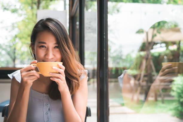 mulher jovem asiática alegre beber café quente ou chá apreciá-lo enquanto está sentado no café. mulher asiática feliz atraente segurando uma xícara de café. - chá bebida quente - fotografias e filmes do acervo