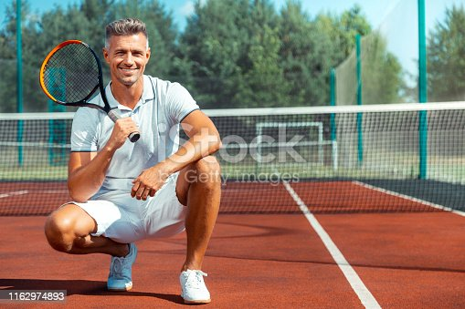 Athletic man smiling. Cheerful athletic man wearing white sneakers smiling after training on tennis court