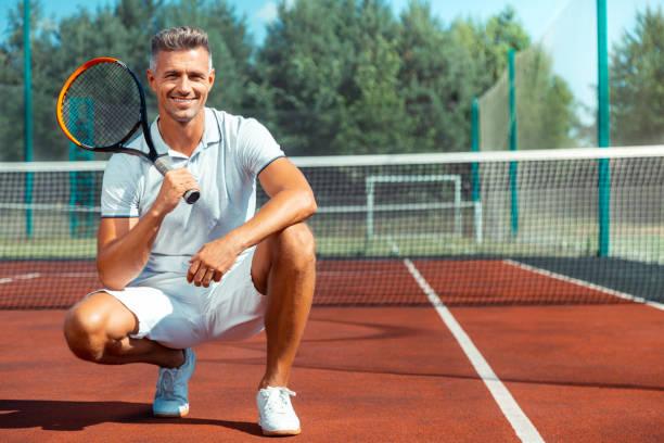 Fröhlicher athletischer Mann lächelnd nach dem Training auf dem Tennisplatz – Foto