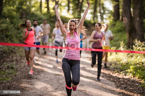 Happy athletic woman running through finish line and celebrating victory with her arms raised.