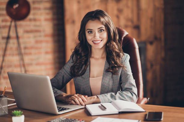 Cheerful attractive adorable stylish beautiful classic trendy business lady sitting in front of laptop at work place, station Cheerful attractive adorable stylish beautiful classic trendy business lady sitting in front of laptop at work place, station administrator stock pictures, royalty-free photos & images