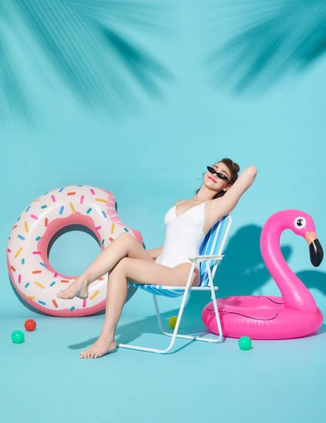 Fröhliche attraktive fröhliche schöne Frauen in schönen Bademode gekleidet sitzen auf einem Strandkorb und Gummiring auf hellblauem Hintergrund. – Foto
