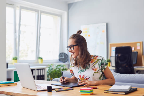 Cheerful attractive young female graphic designer smiling and working at her desk in modern office Cheerful attractive young female graphic designer smiling and working at her desk in modern office design professional stock pictures, royalty-free photos & images